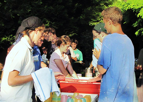 Young people washing dishes together outdoors