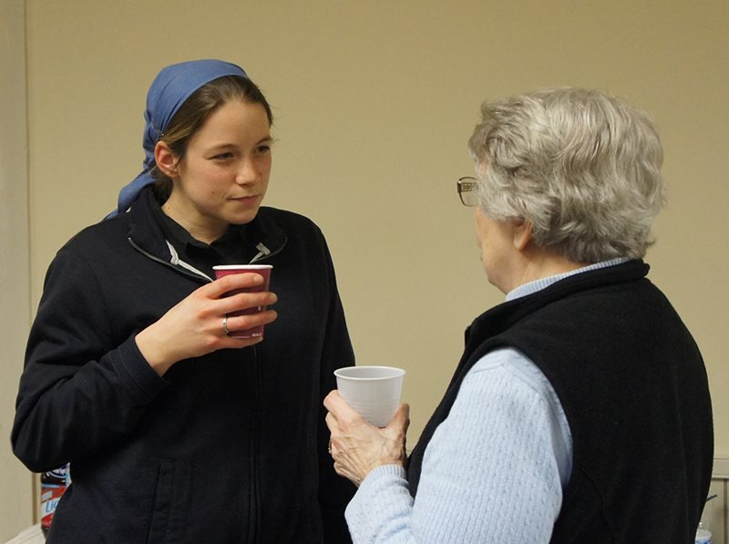 a young woman from an intentional Christian community conversing with a neighbor
