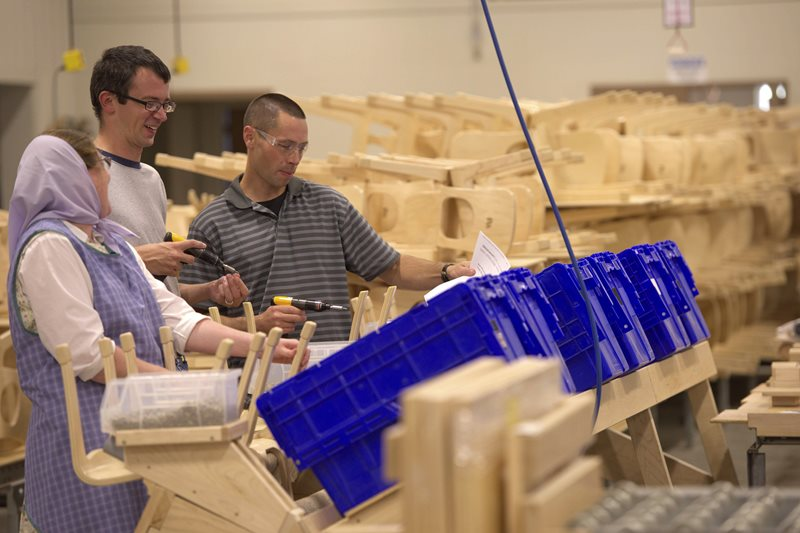 three adults working together in a Community Playthings work shop