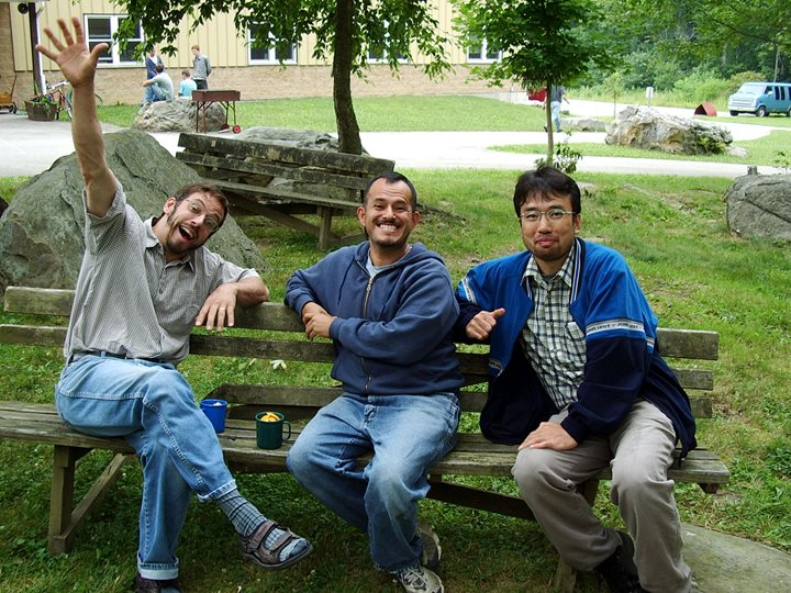 An image of three smiling brothers sitting on a bench outdoors