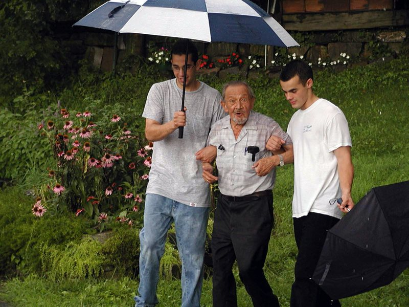 Two young men help and elderly man through the rain under an umbrella