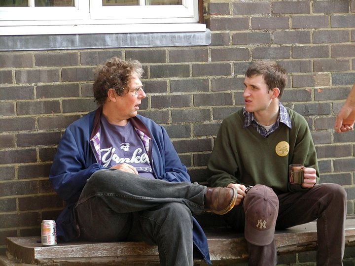 An image of a middle aged man talking to a young man outdoors