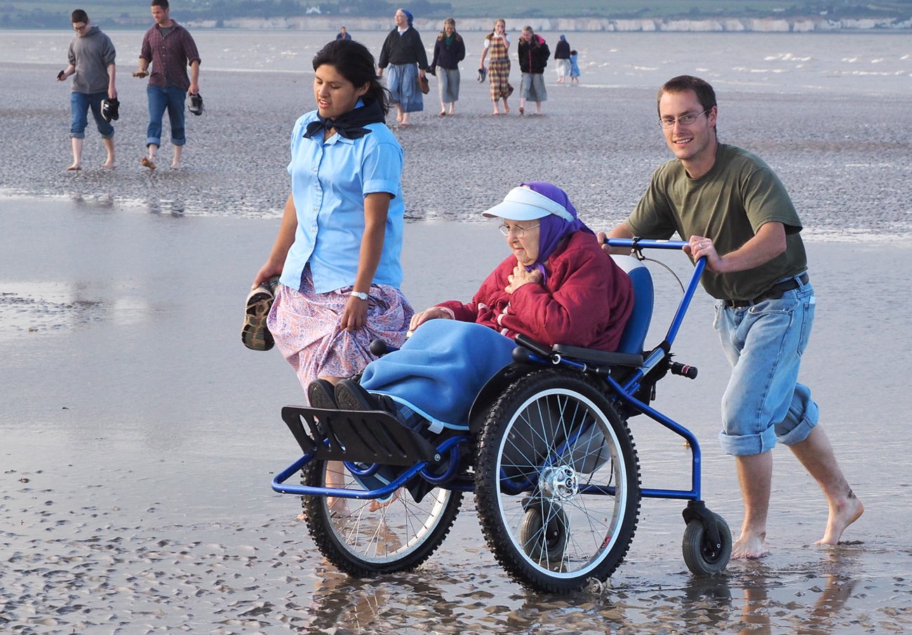a young man and woman pushing a grandmother's wheelchair across the beach