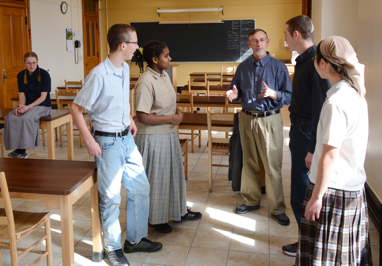 high school students talking with a teacher after class at the Mount Academy