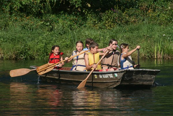 a group of children rowing on a small pond