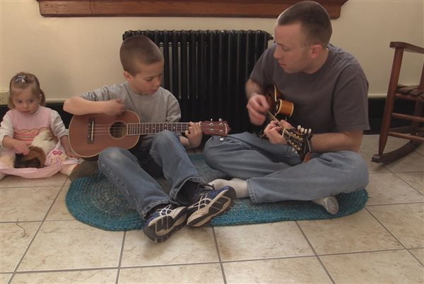 Father playing on the floor with two children