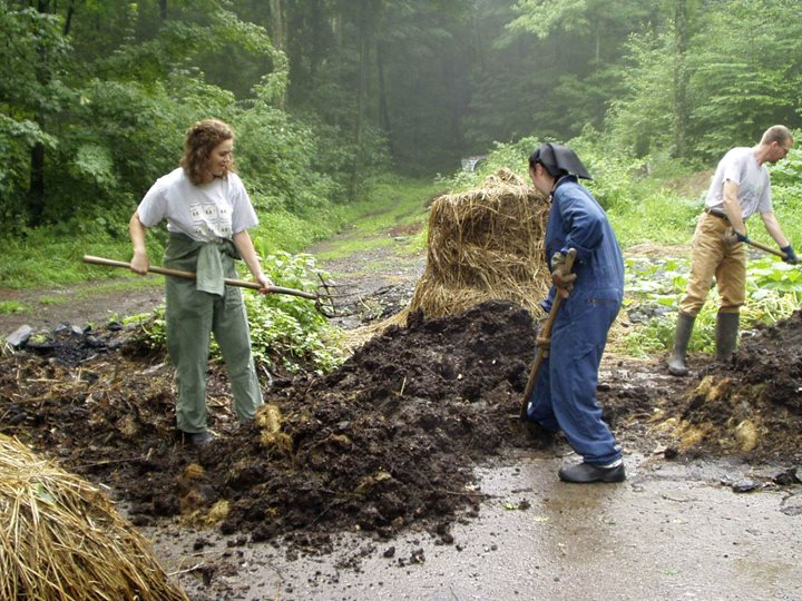 An image of a Bruderhof sister in coveralls shoveling compost with some visitors
