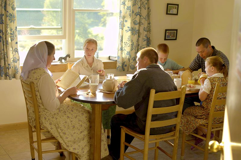 A Bruderhof family sits around the dining table in their apartment and shares a meal and a good story book