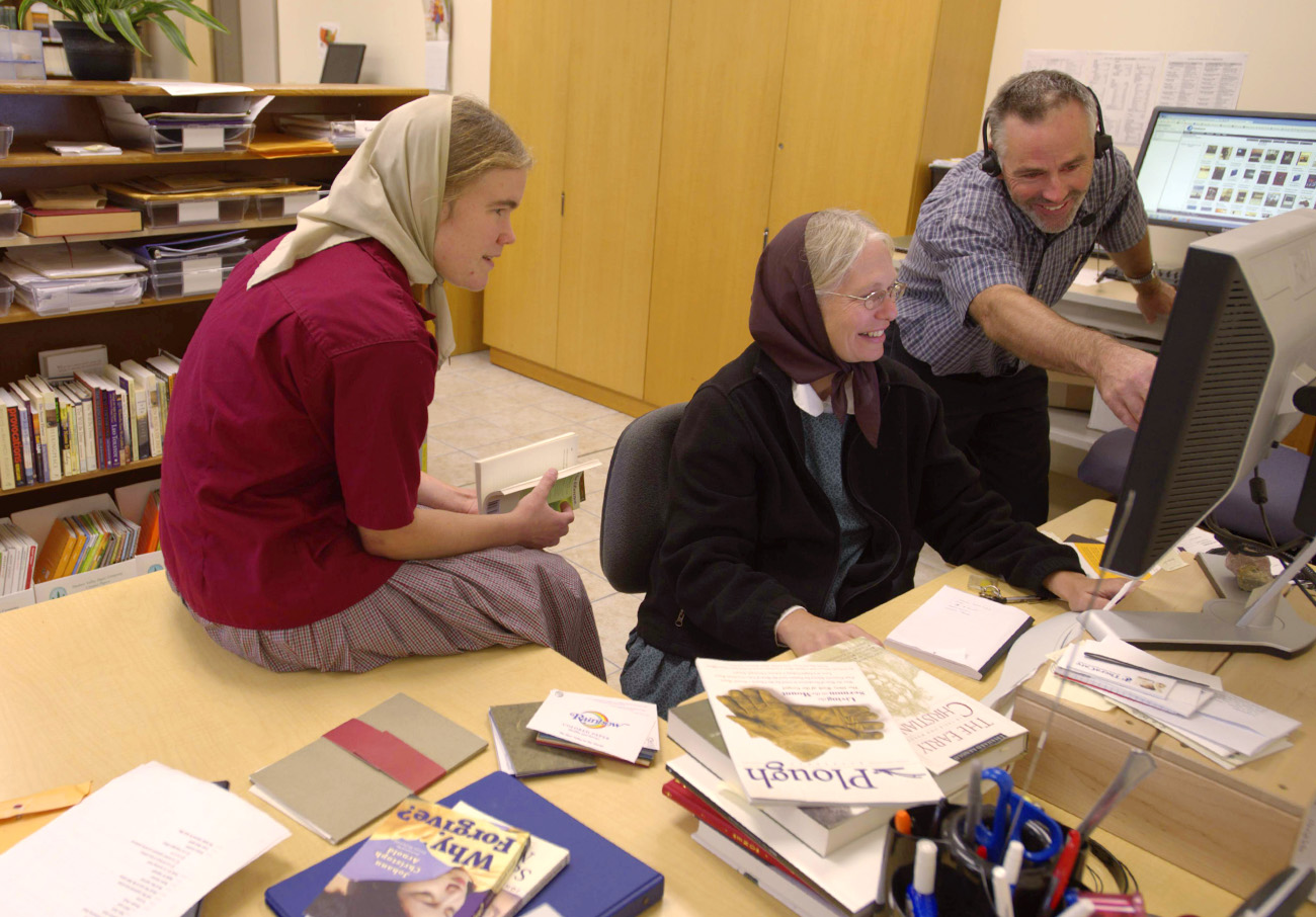 Three Bruderhof members reviewing a book layout on a computer in the Plough Publishing House office