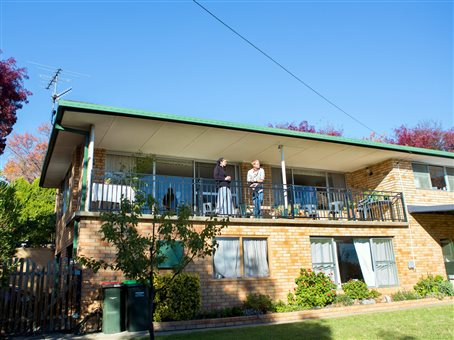An image of  a young man and woman standing on the front porch of the Armidale house