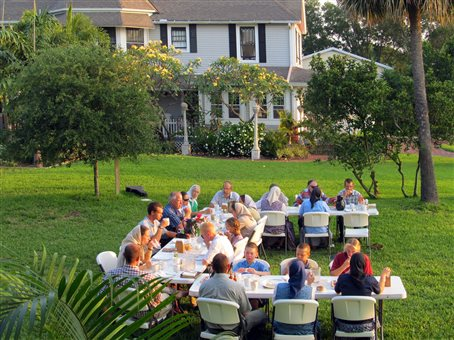 An image of the Bayboro community members enjoying a meal outdoors on their front lawn