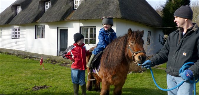 An image of a little girl riding on a pony with her dad holding the lead rope and her older brother looking on