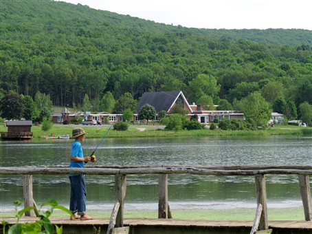 An image of a school age boy fishing on the boardwalk on the edge of the lake at Bellvale Bruderhof