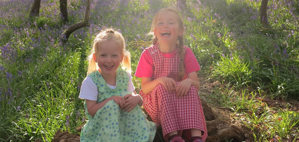 two young girls laughing together in a bluebell woods