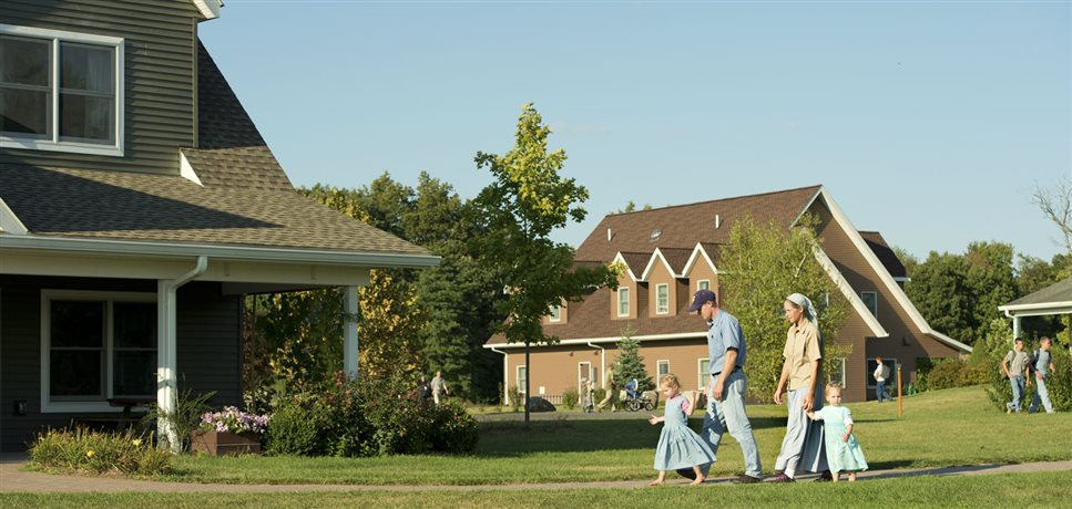 A photo of a family walking home from daycare at the end of the day at Foxhill Bruderhof