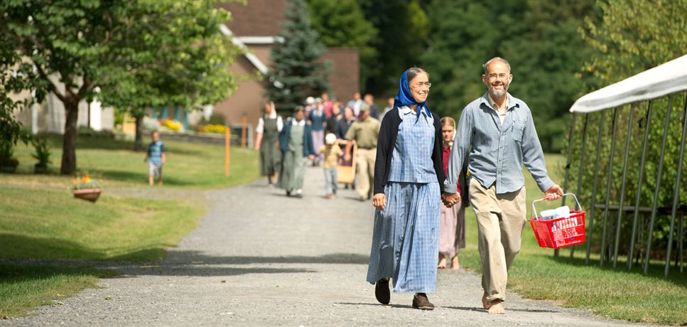 An image of a middle aged couple walking down a dirt road with a shopping basket