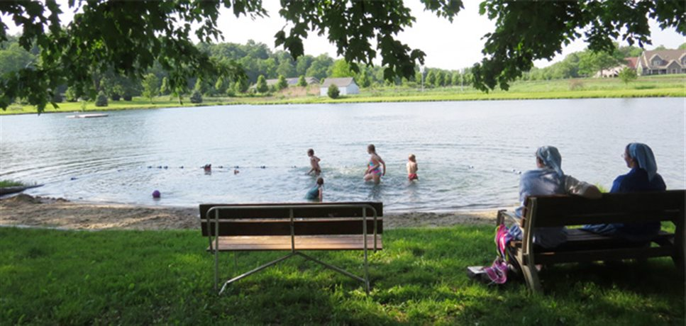 two women watching their children playing in a swimming pond at the Fox Hill Bruderhof