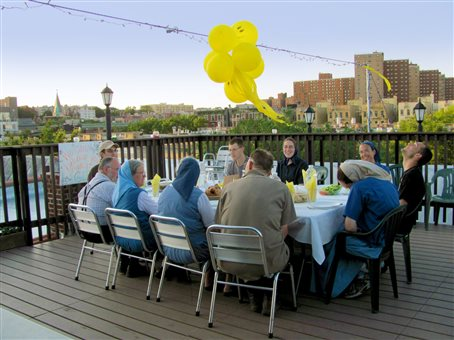 An image of a graduation celebration on the roof of the Harlem Bruderhof house