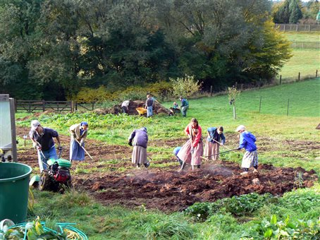 An image of young people turning compost in for the garden at the Holzland Bruderhof