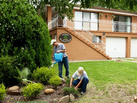A photo of two people tending the garden outside the main house at the Inverell Bruderhof