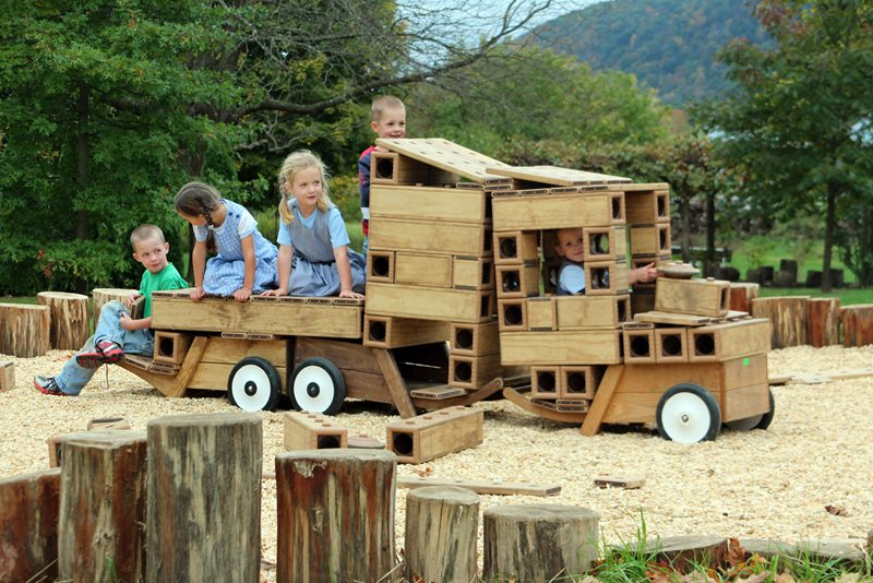 An image of five children playing outdoors on truck constructed out of Outlast playing blocks from Community Playthings at Maple Ridge Bruderhof