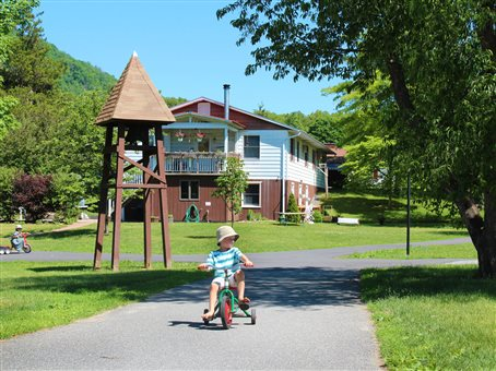 An image of a boy riding a tricycle through the Maple Ridge Bruderhof property