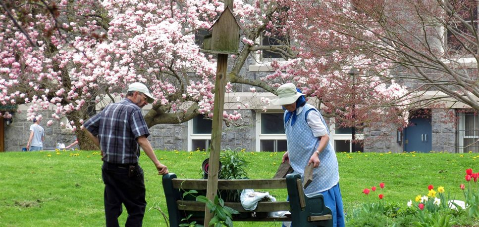 A photo of a Bruderhof couple tending to the gardens around the Mount community