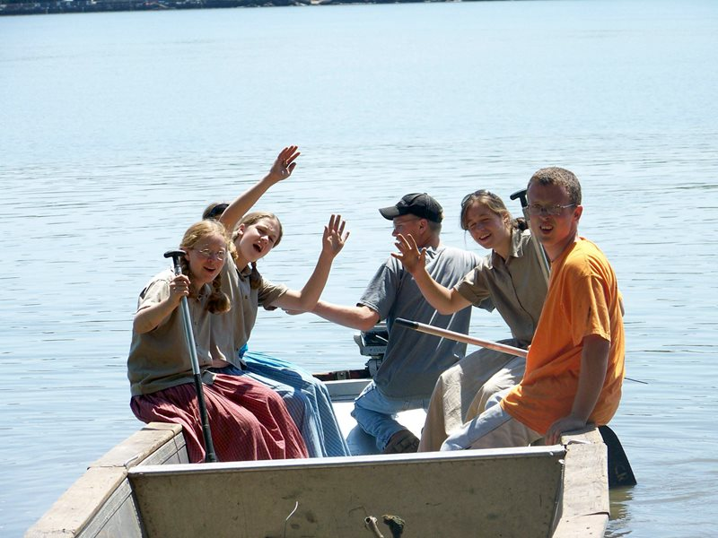 A photo of young people sitting on the rim of a boat in the Hudson River near the Mount Community