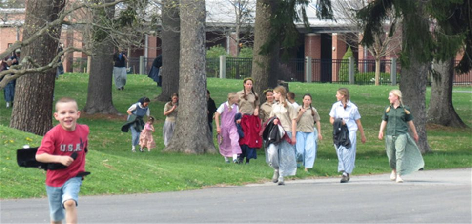 school children coming across a lawn and onto a road at the Mount Bruderhof community
