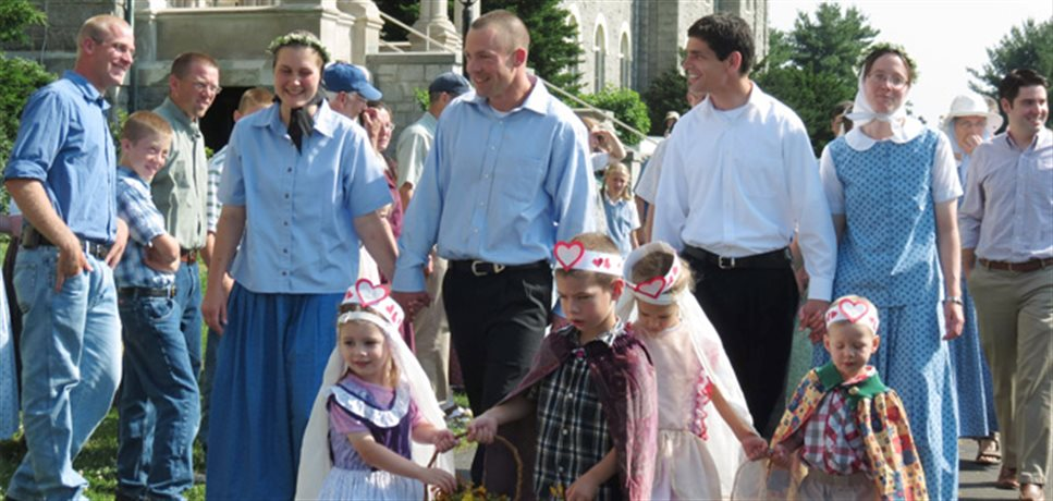 Two engaged couples being led by several young children scattering flowers down the steps of the main building at the Mount Bruderhof community