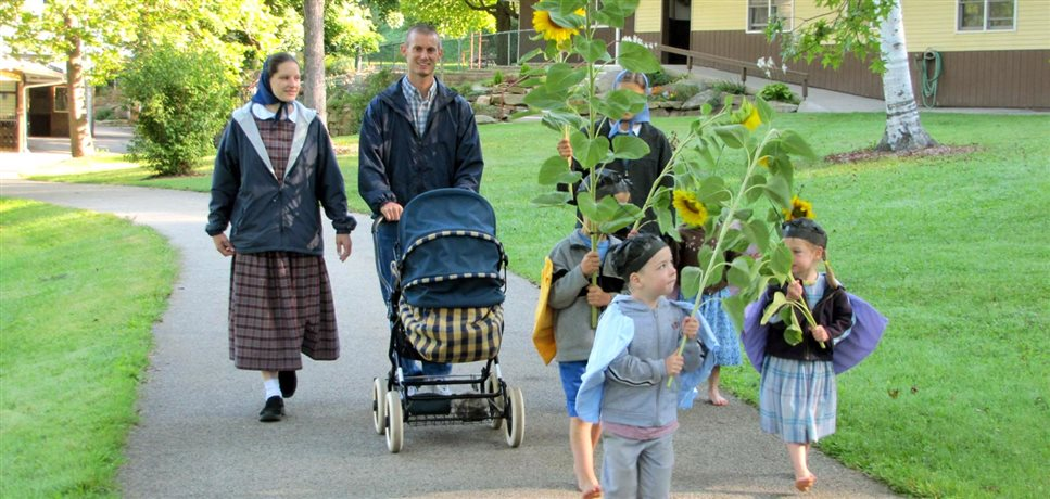 A photo of children carrying tall sunflowers in a procession to welcome a new baby to the daycare at the New Meadow Run Bruderhof