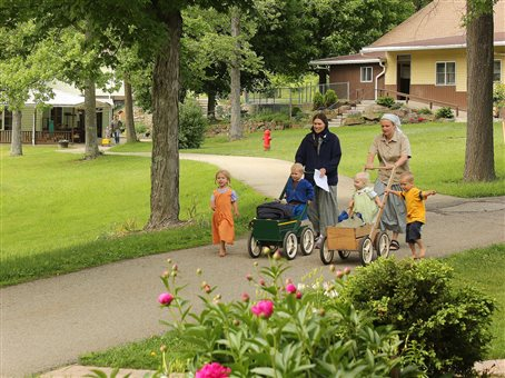 An image of two young mothers taking their children to the daycare center at the New Meadow Run Bruderhof