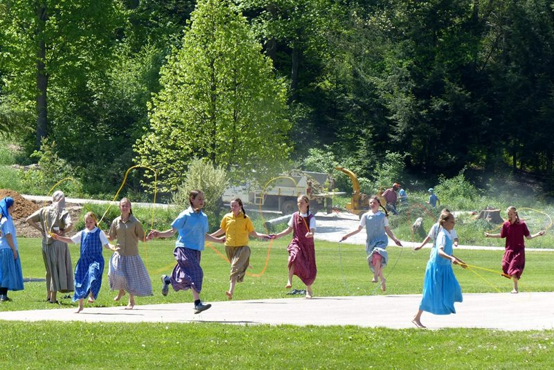 A photo of young Bruderhof girls jump roping at the New Meadow Run Bruderhof