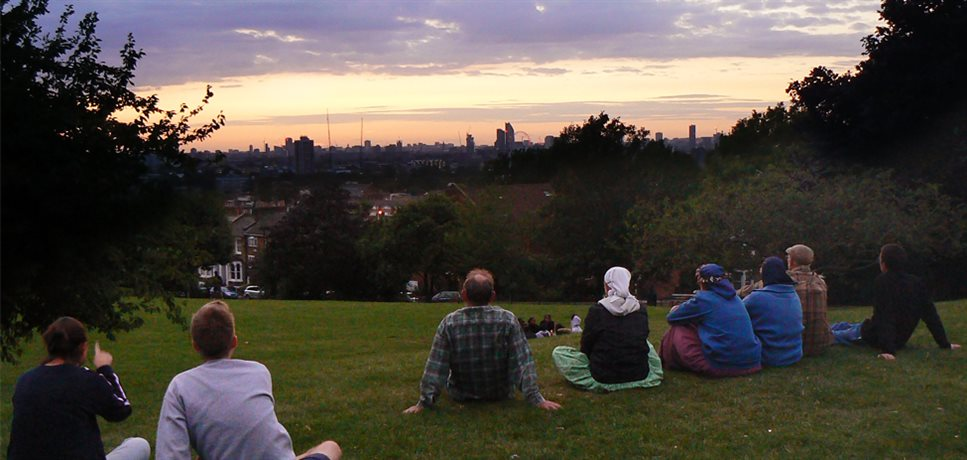 Members of the Peckham community house sitting on a grassy hilltop for an evening gathering