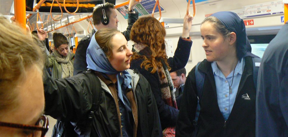 two young women from the Peckham community house on the train going to school