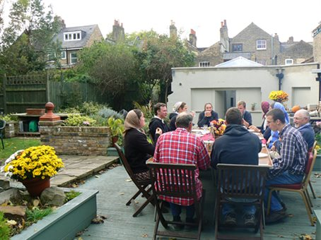 Members of the Peckham community house sharing a meal together outside in the yard