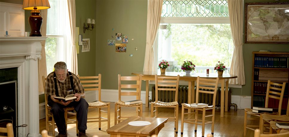 An image of an elderly man reading a book in the meeting room at the Rondout Bruderhof house