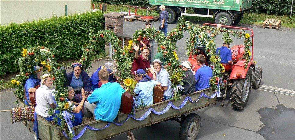 An image of members of the Sannerz Bruderhof community sitting in a festively decorated trailer being pulled a tractor
