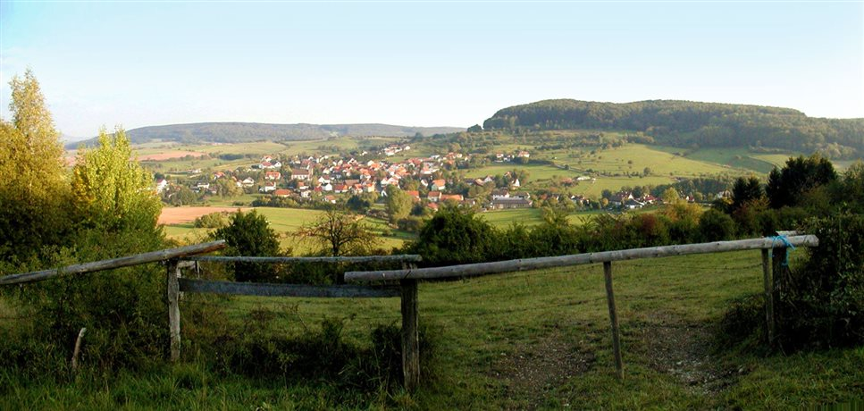 An image of panoramic view of the German countryside with a small village  in the background