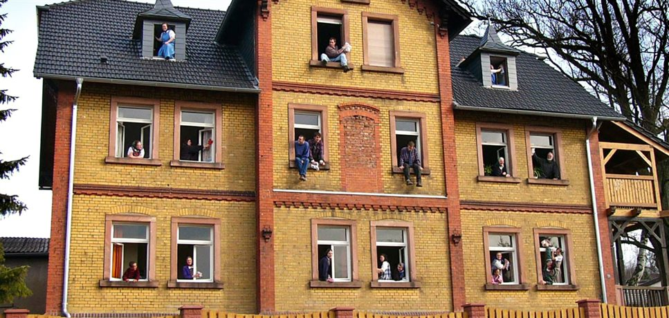 An image of spring cleaning at the Sannerz Bruderhof with people looking out each window of the main house