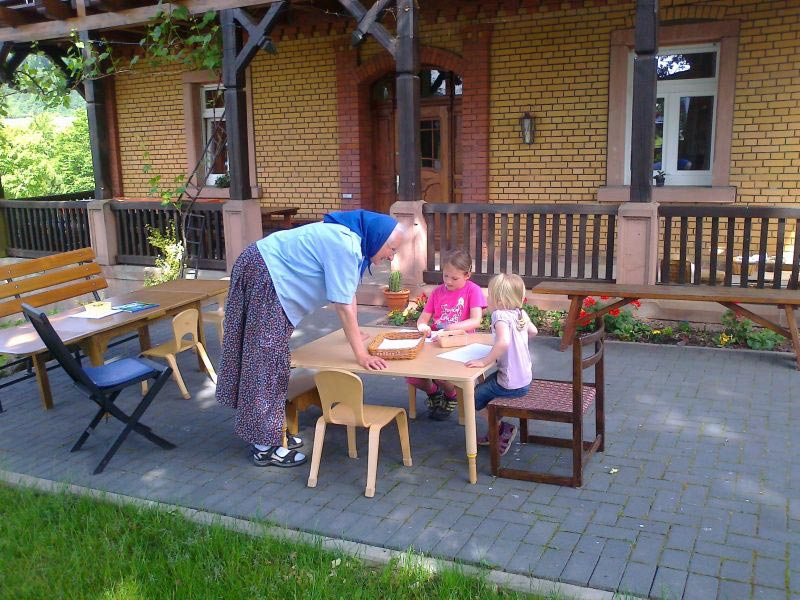 a grandmother watching two young girls drawing pictures outside the Sannerz community house