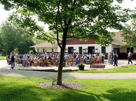 An image of the Spring Valley Bruderhof community members gathering and sitting in chars in a circle out in front of the main dining hall building