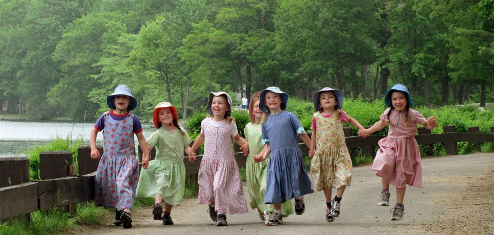 An image of six happy Bruderhof preschool girls holding hands and skipping down a road