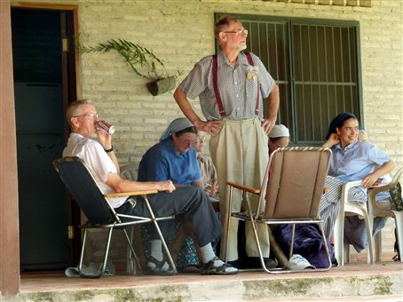 An image of Bruderhof members relaxing on the front porch of the main house at Villa Primavera