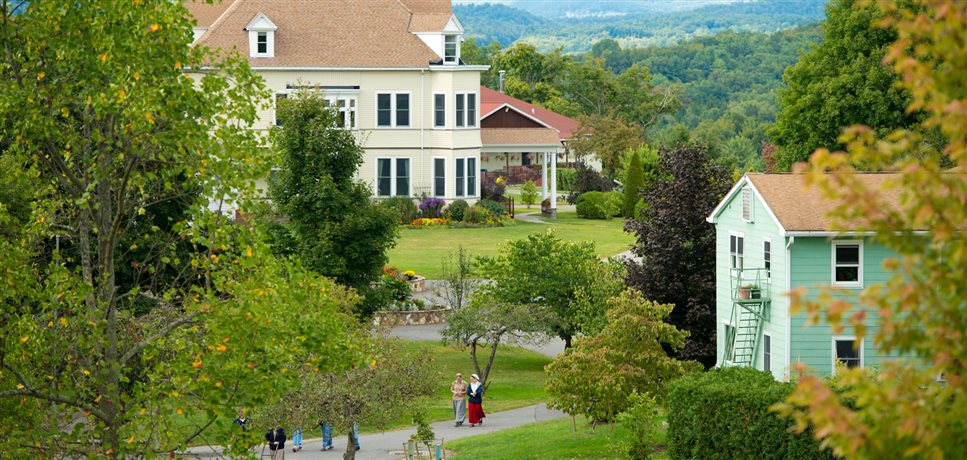 An image of people walking through the grounds of the Woodcrest Bruderhof with mountains in the distance