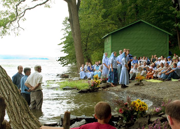 An image of a group of young adults giving their confession of Christian faith before entering the river to be baptized