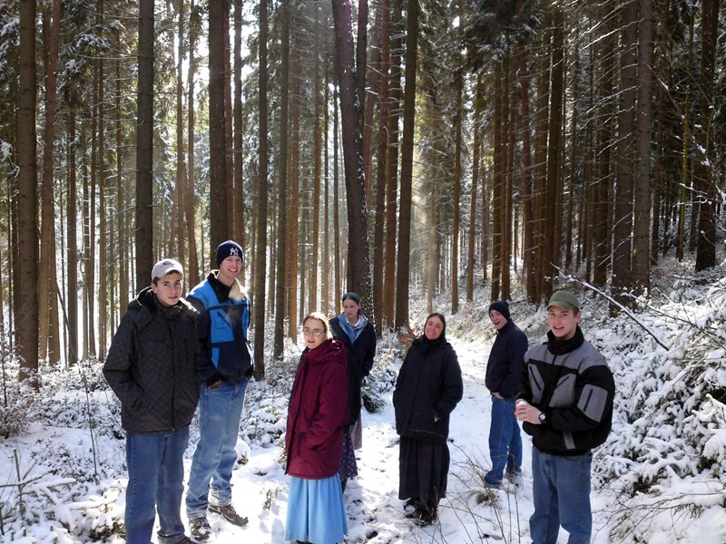A group of adults on a winter walk through a forest