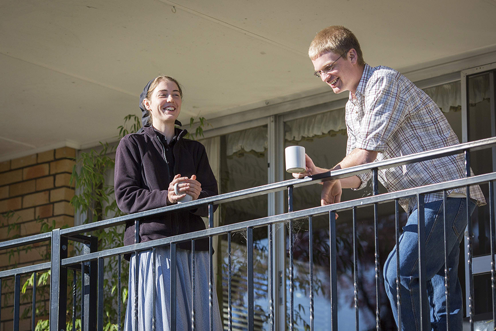 a young man and woman talking together at the Armidale Bruderhof in Australia