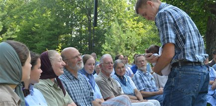 members of an intentional Christian community welcoming a new baby