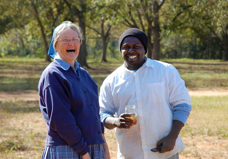 An image of a Bruderhof woman sharing a good laugh with a member of Koinonia Farms in Georgia